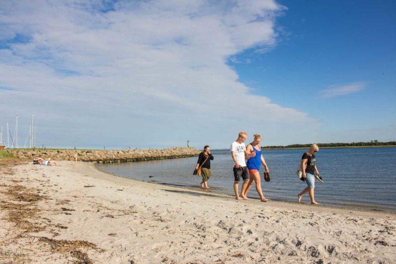Turister på Udbyhøj strand på en solrig dag med 30 grader, hvid sand og blåt klart vand