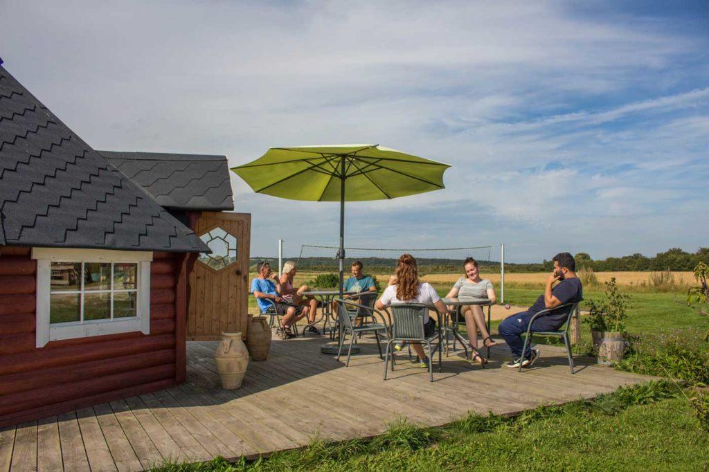 Gæster siddende i Solen på bålhyttens træterrasse med udsigt til beachvolleybanen