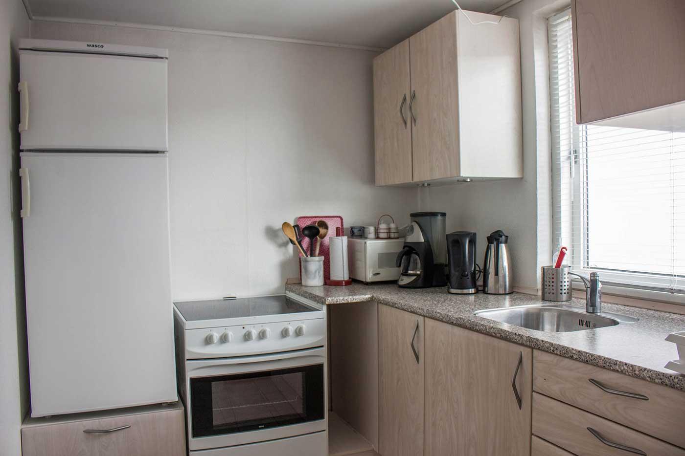 Køkkenet med kølefryseskab, ovn, komfur, elkedel, kaffemaskine mv.