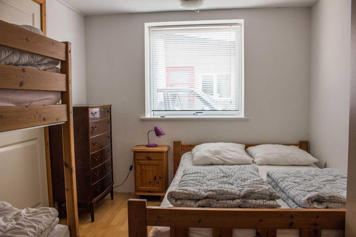 Lejlighedens eneste soveværelse med dobbeltseng, køjeseng og stort klædeskab