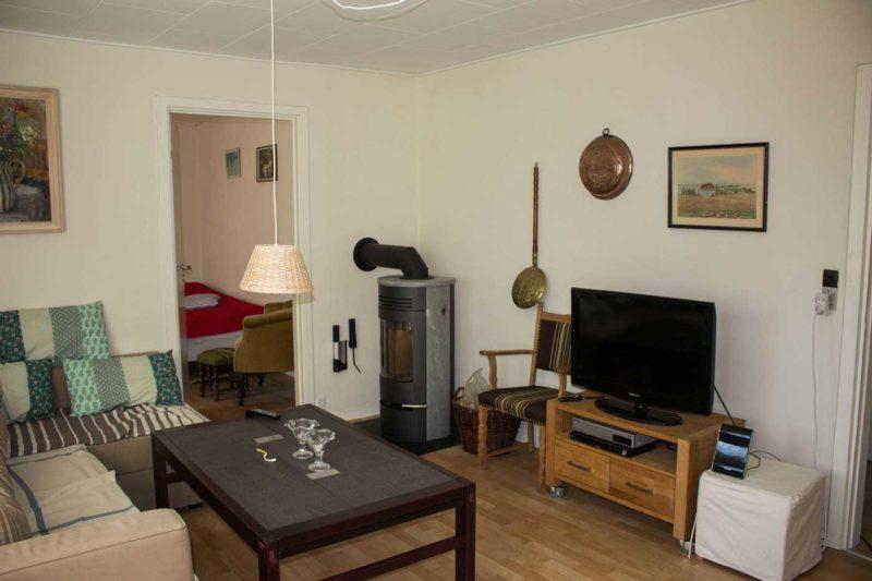 Stuen i stueplan med adgang til et af værelserne og gang til køkken og badeværelse