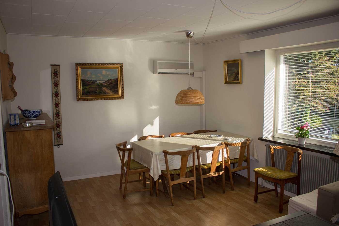 Spisepladser i stuen i stueetagen med Solen i de store vinduer