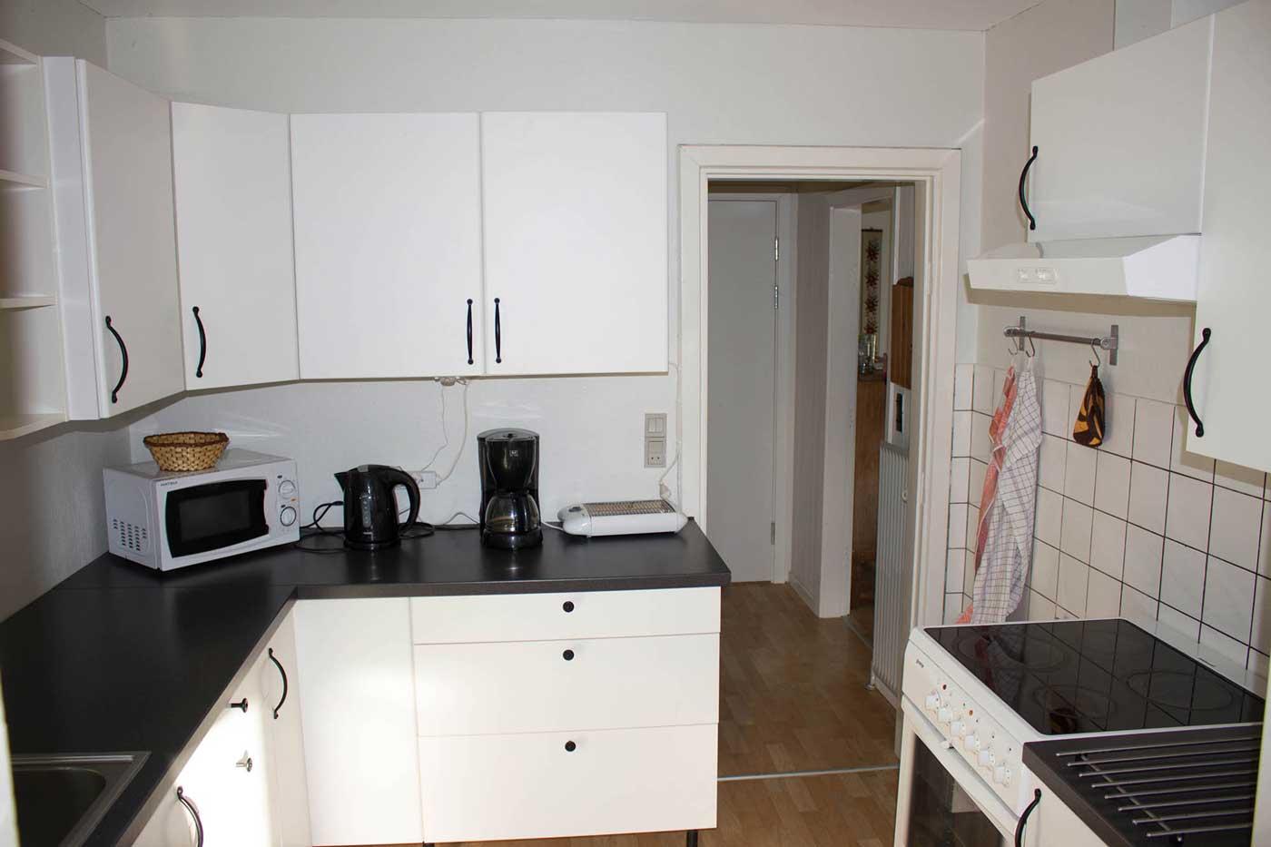 Køkkenet i stueetagen med komfur, kogeplader, kølefryseskab, kaffemaskine, mikroovn og elkedel