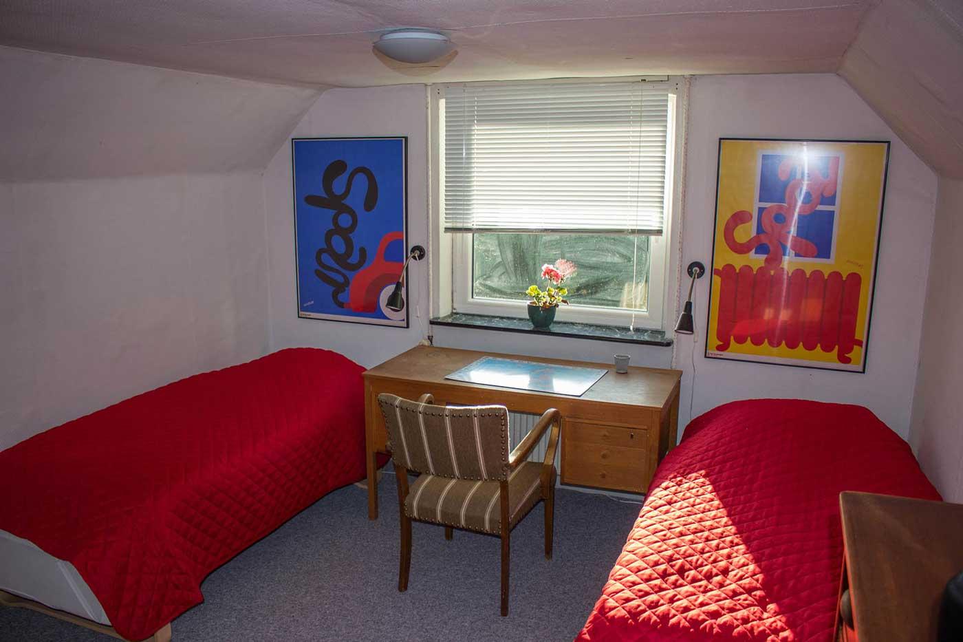 To enkeltsenge og plads ved skrivebord i et af værelserne på 1. sal