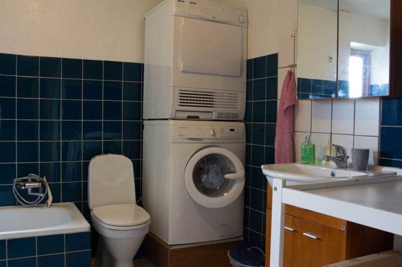 Ferielejlighedens badeværelset med vaskemaskine, tørretumbler, badekar og bruseniche