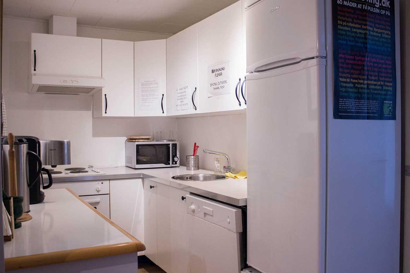 Køkkenet med kølefryseskab, mikroovn, elkedel, kaffemaskine, opvaskemaskine mv.