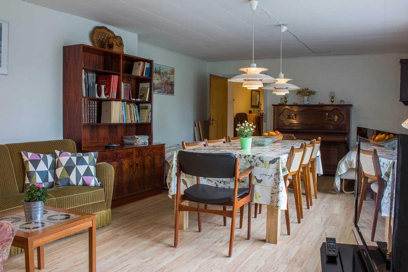 Lejligheden store stue med sofagruppe, stort spisebord og to sengepladser