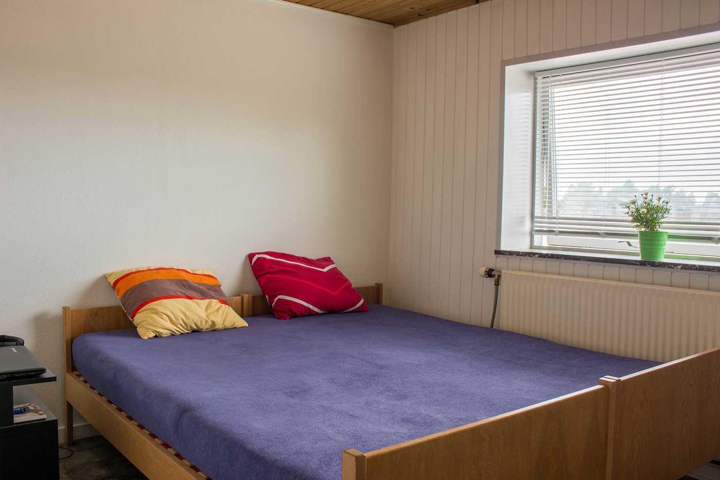 Det ene soveværelse med dobbelt seng ved indgangen til lejligheden