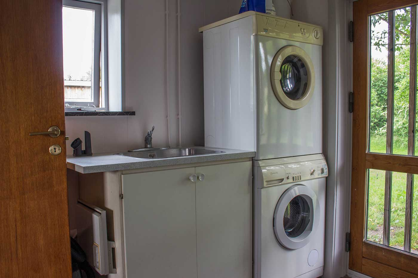 Bryggers ved indgang til lejligheden med vask, vaskemaskine og tørretumbler