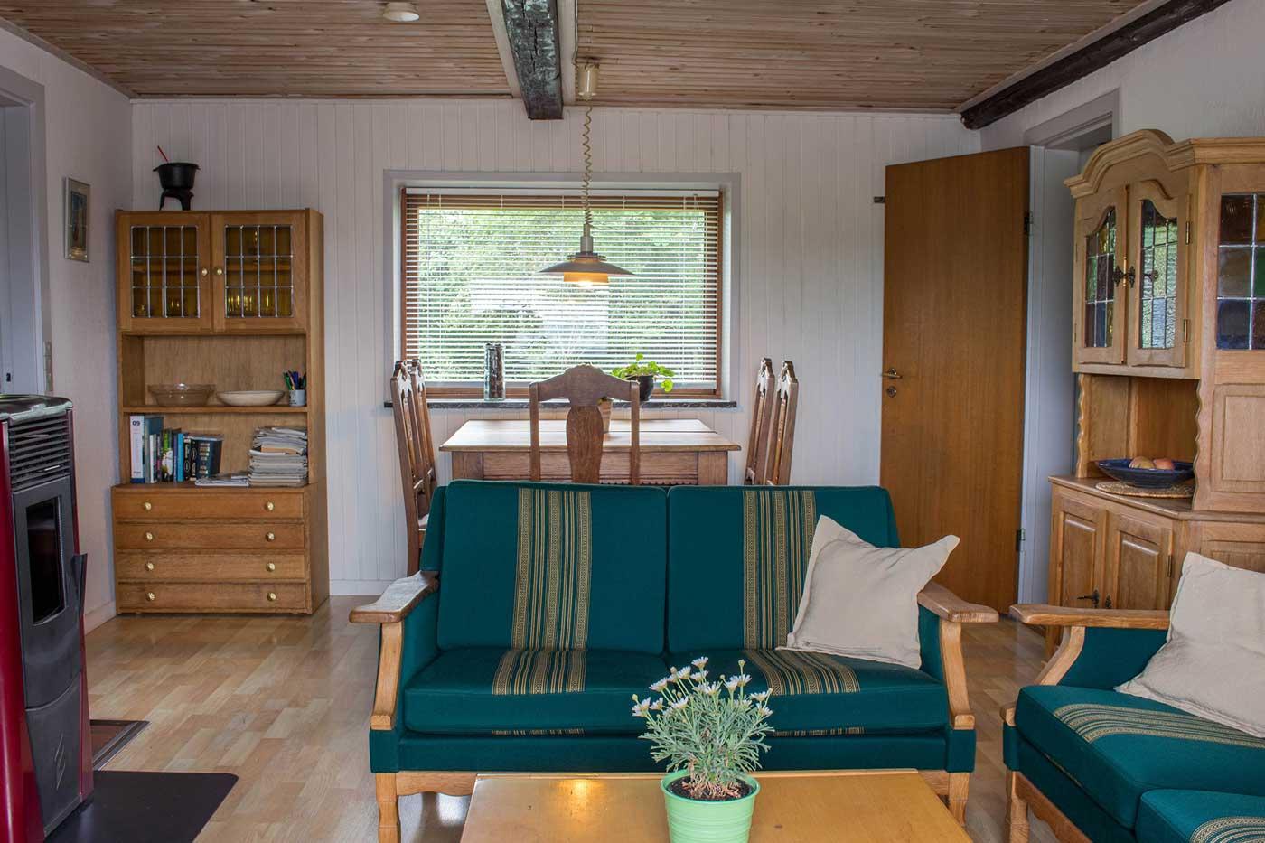 Stuen med pilleovn, sofagruppe, TV og adgang til badeværelse, køkken og soveværelse